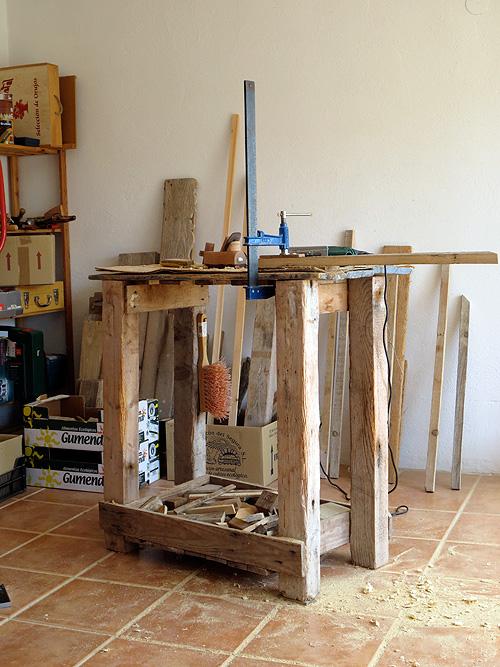 Banco de trabajo de carpintero artesanal con gato sujetando listón de madera