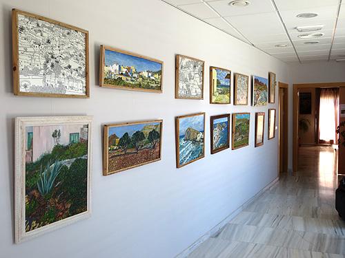 Vista del pasillo con pinturas y dibujos con marcos de madera reciclada