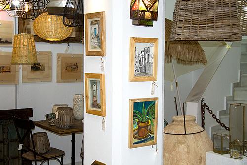 Los cuadros en pequeño formato se funden entre la decoración de la tienda