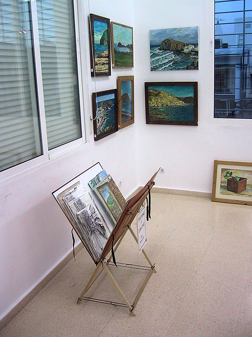 Esquina de la sala con carpeta de pinturas y dibujos sin enmarcar