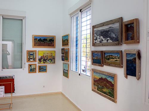 Vista de la exposición con pinturas y dibujos con marcos de madera reciclada