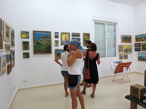 Público visitando la exposición y disfrutando del aperitivo