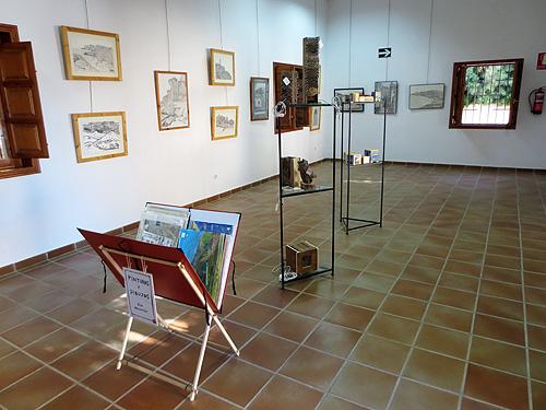 Vista de la exposición con trípode y estantería con  objetos de madera reciclada