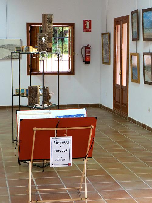 Trípode con pinturas y dibujos plastificados en el centro de la sala